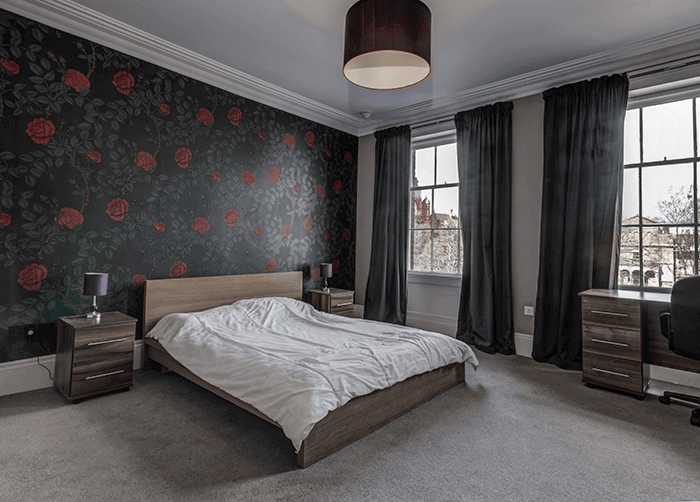 Spacious bedroom with dark wallpaper and curtains