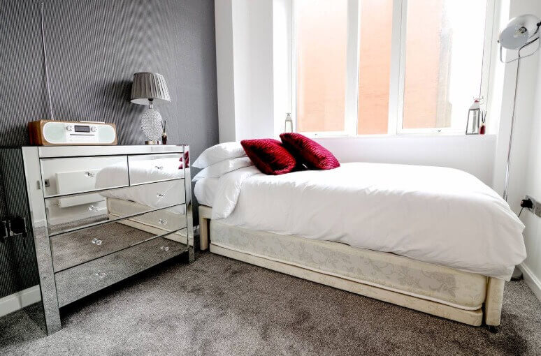 White bed with red pillows and mirrored drawers in Manchester