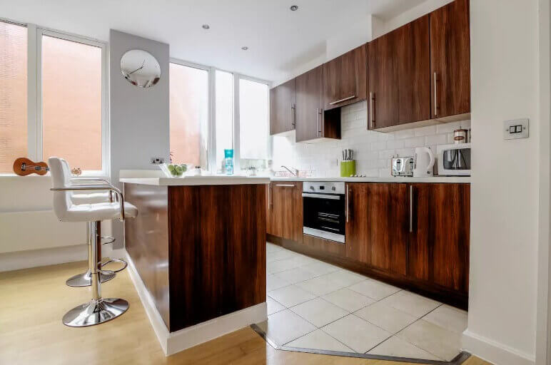 Open wood-panneled kitchen with island in Manchester